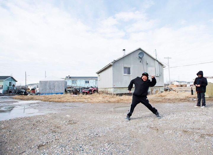 Teenage boys throw rocks in the northern Ontario First Nations reserve in Attawapiskat, Ont., on April 16, 2016.