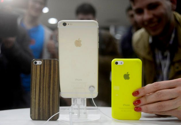 Customers compare the size of an iPhone 6 Plus and an iPhone 5S in