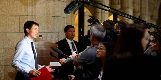 Prime Minister Justin Trudeau pauses to talk to media as he arrives to a caucus meeting on Parliament...