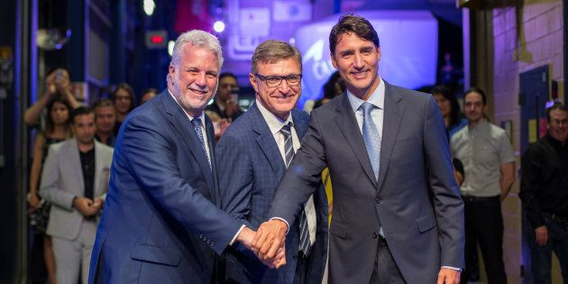 Prime Minister Justin Trudeau poses with Quebec Liberal Leader Philippe Couillard and CAE Inc. president and CEO Marc Parent after a news conference at CAE Inc., in Montreal on Aug. 8, 2018.