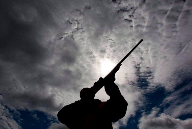 A man checks the sight of his rifle at a hunting camp property in rural Ontario, west of Ottawa, on Sept....