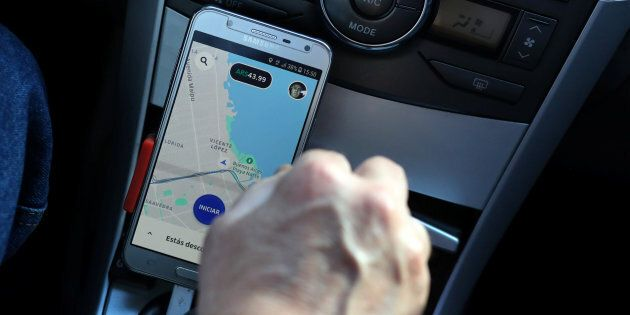 Uber driver Juan Carlos uses his application map on his cellphone as he drives his car in Buenos Aires...