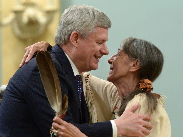 Stephen Harper hugs Elder Evelyn Commanda-Dewache, a residential school survivor, during the closing...
