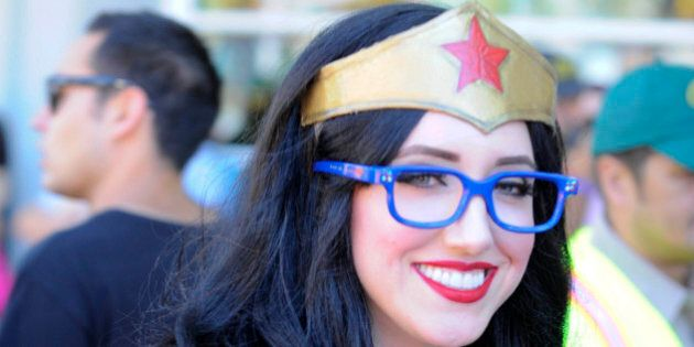 Dressed as Wonder Woman, Lindsay Stanley, walks in front of the convention center before waiting in line...