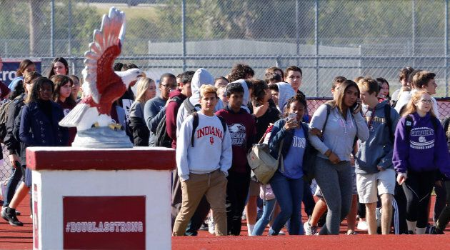 Students walk out of Marjory Stoneman Douglas High School as part of a National School Walkout to honor the 17 students and staff members killed at the school in Parkland, Florida.