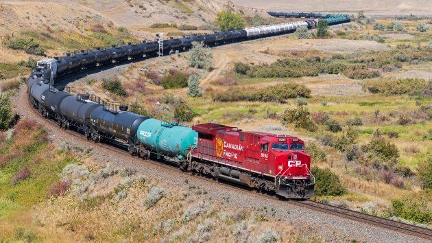 A Canadian Pacific Railway locomotive pulling a long freight train, including tanker railcars, near Medicine...