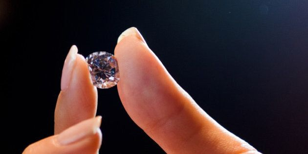 A Sotheby's auction house employee holds 'Premier Blue', the world's largest round fancy vivid blue diamond,...