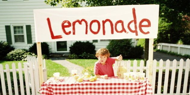 Boy (6-8) selling lemonade from sidewalk