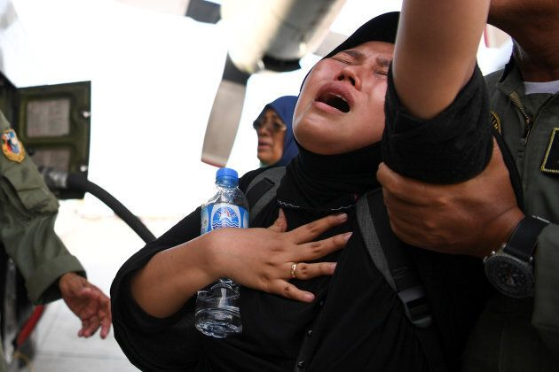 A woman cries as she waits to be evacuated by military aircraft following an earthquake and tsunami,...