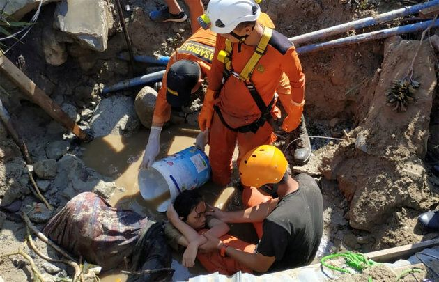 Search and rescue workers help rescue a person trapped in rubble following an earthquake and tsunami...