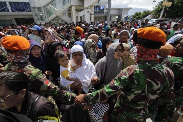 Residents line up Sunday to board a Hercules aircraft belonging to the Indonesian Air Force, as they...