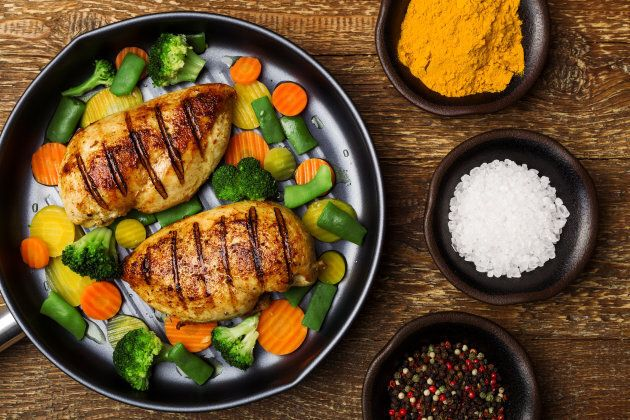 Grilled chicken breast with vegetables in a pan.