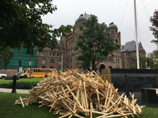 A pile of crosses lies in front of Ontario's legislature on Oct. 1, 2018.