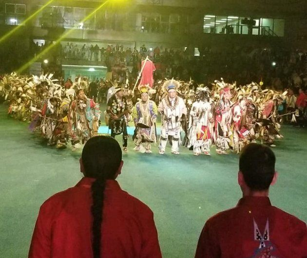 Indigenous men formed a circle around a red dress, meant to symbolize missing and murdered Indigenous...