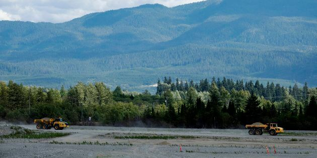 Two dump trucks work at the proposed site for an LNG Canada work camp, in Kitimat, B.C., Aug. 22, 2018....