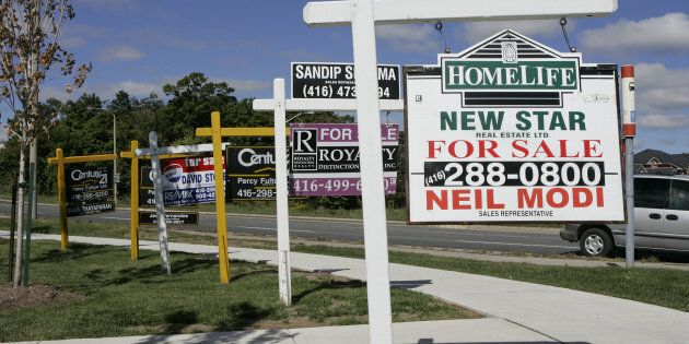 House for sale signs in front of a townhouse complex are seen in Toronto in this file photo. The Canadian...