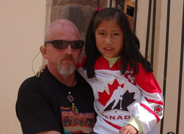 Reeleder poses with a young girl in Peru, who's wearing a hockey jersey donated by Hayley