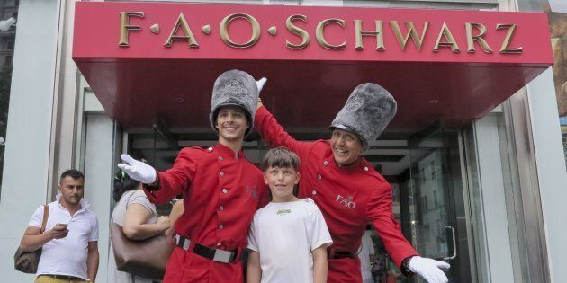 A boy has his photo taken outside the FAO Schwarz toy store in New York City, July 15, 2015. A pop-up...