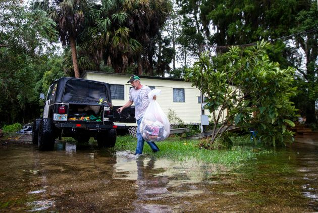 Mitchell Pope tries to salvage what he can from his mobile home as Hurricane Michael hits on Oct. 10,