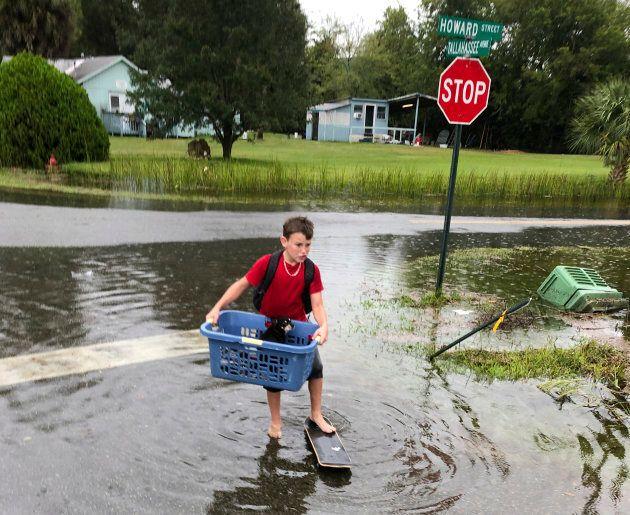 Jayden Morgan, 11, evacuates his home as water starts to flood his neighborhood in St. Marks, Fla. on...
