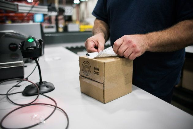 A worker applies a shipping label to a package of cannabis products at the Ontario Cannabis Store distribution...