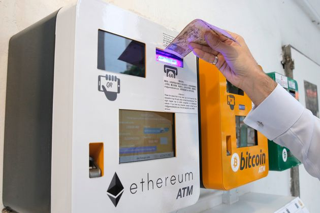 A man uses the Ethereum ATM in Hong Kong, Friday, May 11,