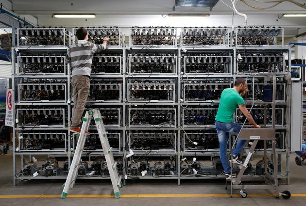 Employees work on Bitcoin mining computers at Bitminer Factory in Florence, Italy on April 6,