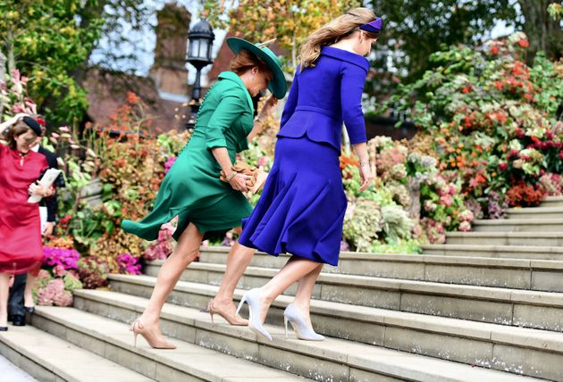 Britain's Princess Beatrice, right, and her mother, Sarah Ferguson, left, battle the gusty winds up the...
