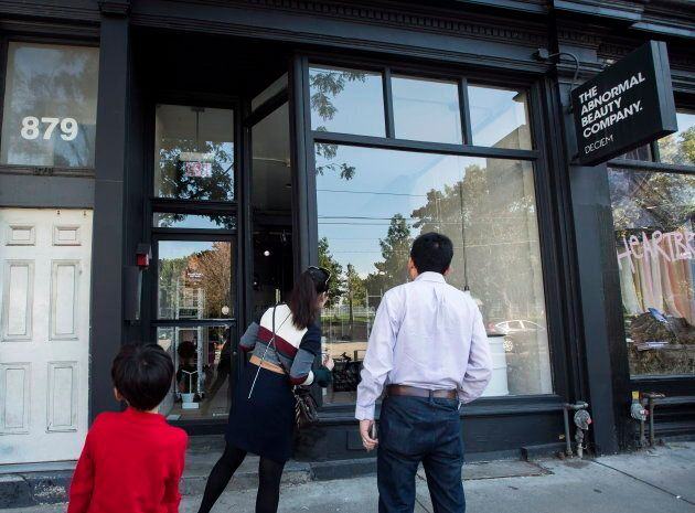 People looking inside a closed Deciem store in