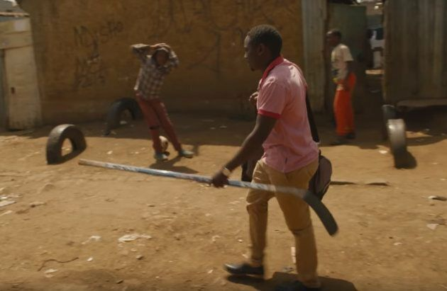 A member of the Kenya Ice Lions walks through the streets of Nairobi with a hockey stick.