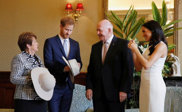 Prince Harry and Meghan, Duchess of Sussex react as they receives traditional Australian hats from Australia's...