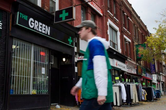 People walk past a cannabis dispensary in Toronto on Oct. 15,