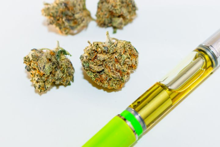 Marijuana bud with THC oil filled vape pen.