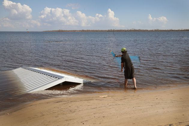 A man works around debris tossed into the water by Hurricane Michael as he fishes in East Bay on Oct....