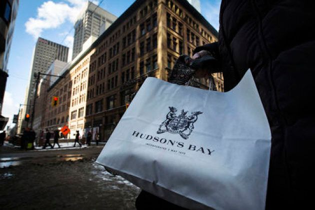 A woman holds a Hudson's Bay shopping bag in front of the Hudson's Bay Company flagship department store...