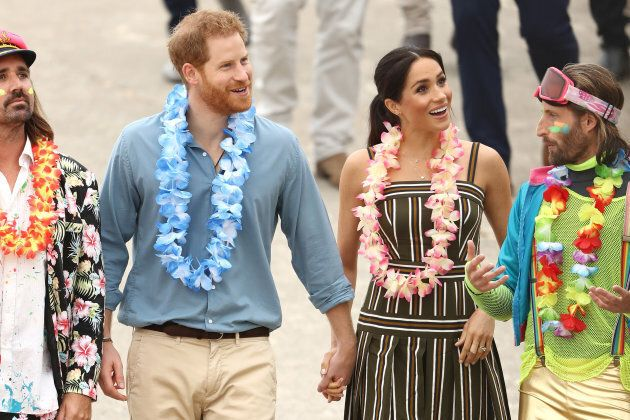 Meghan and Harry with some colourfully-clothed Australians.