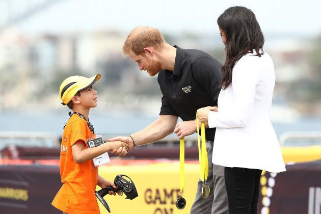 Harry and Meghan give medals to winners of the Young Drivers Challenge on Saturday.