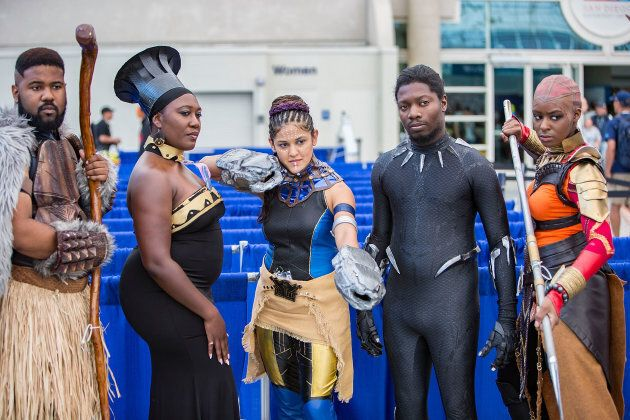 Fans dressed as characters from Marvel's Black Panther movie attend Comic-Con International on July 20,...