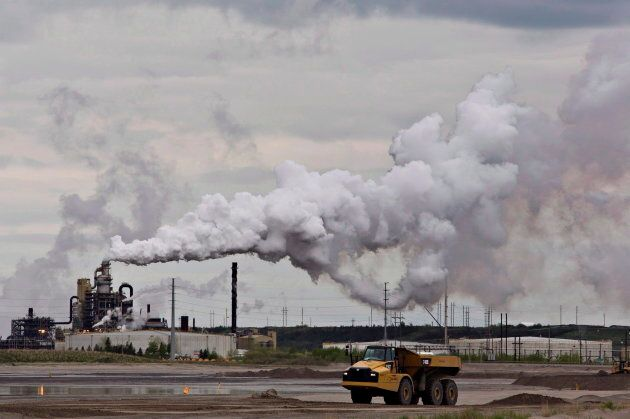 A dump truck works near the Syncrude oil sands extraction facility near the city of Fort McMurray, Alta.,...