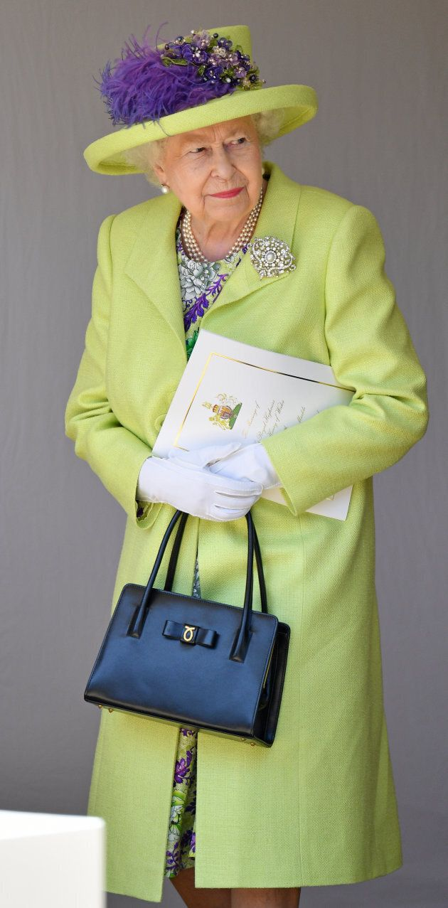 Queen Elizabeth looking quite regal in a lime green coat and hat at Markle and Prince Harry's