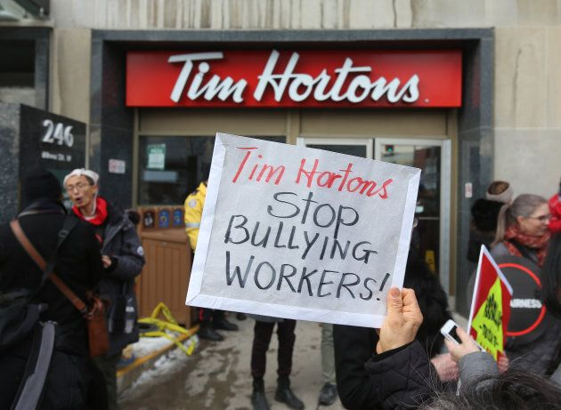 Protesters hold signs outside a Tim Horton's in Toronto on January 10,