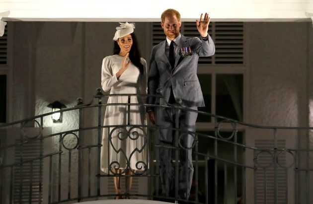 Harry and Meghan wave from a balcony as they arrive for an official dinner at the Grand Pacific Hotel on Tuesday.