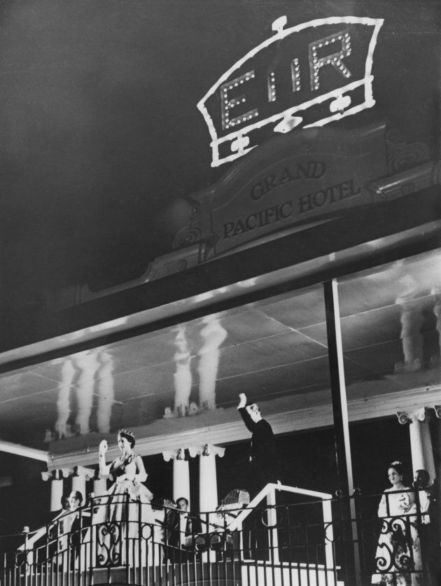 Queen Elizabeth II and Prince Philip wave to crowds from the balcony of the Grand Pacific Hotel in Suva, Fiji, on Dec. 28, 1953.