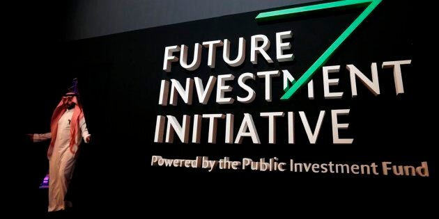 A Saudi participant walks in front of a banner for the Future Investment Initiative conference, in Riyadh,...