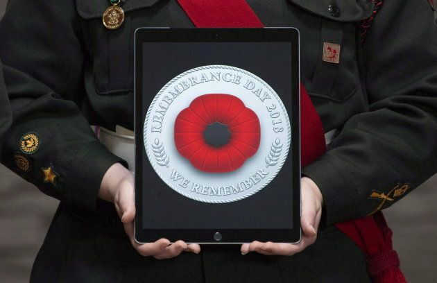 A cadet holds a tablet showing the digital poppy during a ceremony at the Beechwood National Memorial...