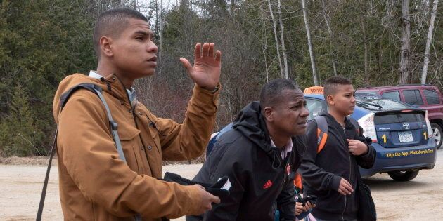 A man and his family speak with RCMP officers near Champlain, NY. on April 18,