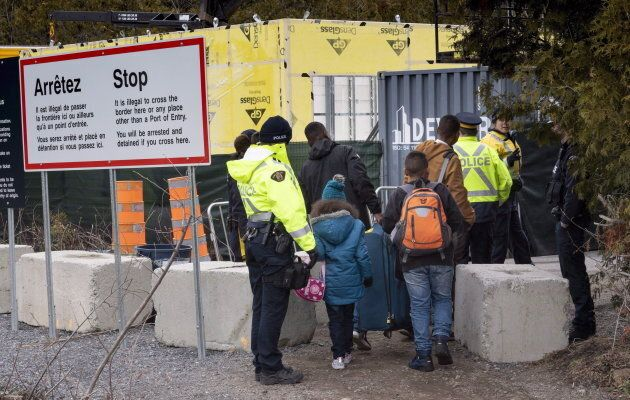 A family is arrested by RCMP officers as they cross the border into Canada near Champlain, N.Y. on April...