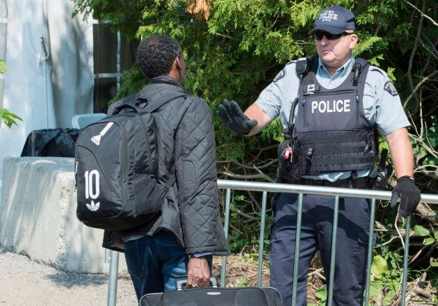 An asylum seeker is questioned by an RCMP officer as he crosses the border into Canada near Champlain,...