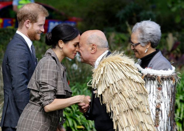 """Meghan Markle receives a """"hongi,"""" a traditional Maori welcome, on the lawns of Government House in Wellington, New Zealand on Sunday."""
