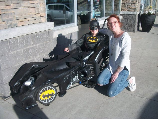 Troy poses with his barber Katie, proudly showing off the custom Batmobile costume that fits over his